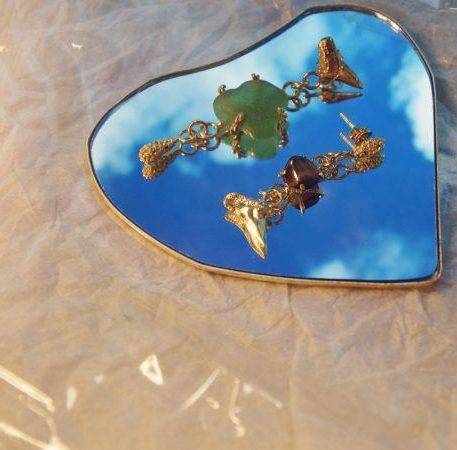 Unequal long earrings with sea glass and tiger eye in gold on mirror.
