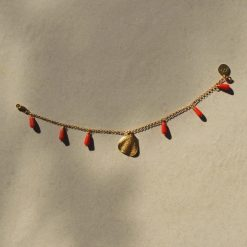 Pallas bracelet in gold with coral colored crystals on beige background